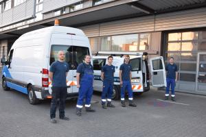 Fünf junge Mitarbeiter stehen vor zwei Transport-Fahrzeugen.